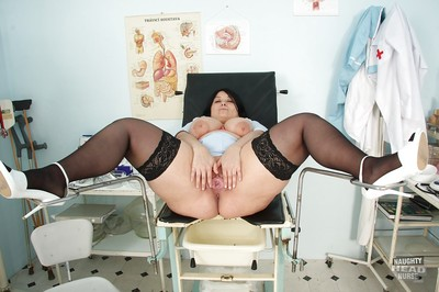 Buxom raiven-haired grown nurse in nylons revealing her jugs and snatch