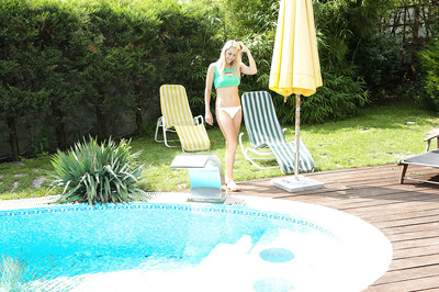 Leggy fairy-haired Christen is sitting at the poolside and playing with puss