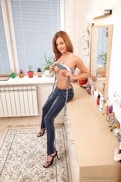 Slight juvenile model in jeans undressing and exposing her tense holes