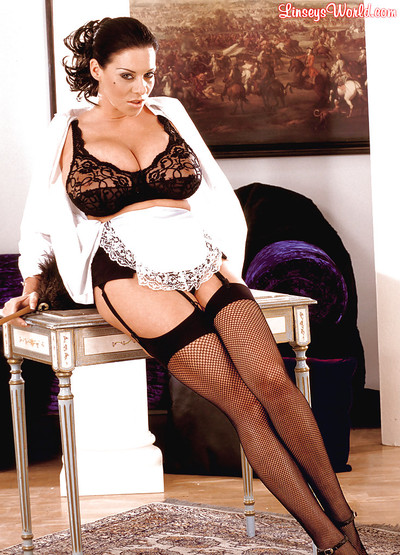 Appealing BBW female house slave Linsey Dawn McKenzie positions in her uniform and high heels.