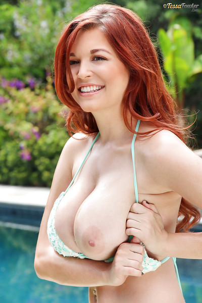 Titsy redhead model Tessa Fowler posing outdoors beside pool in bikini