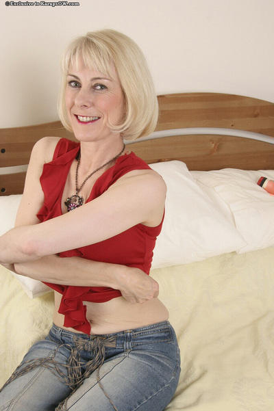 Lively calm fairy-haired in blue jeans undressing and exposing her wavy gash