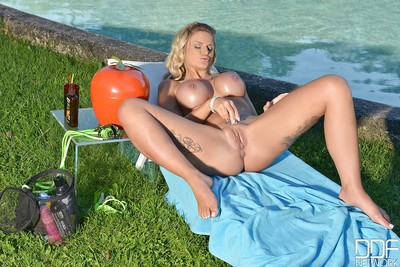Buxom golden-haired Candy Sexton masturbates her moist muff by the pool