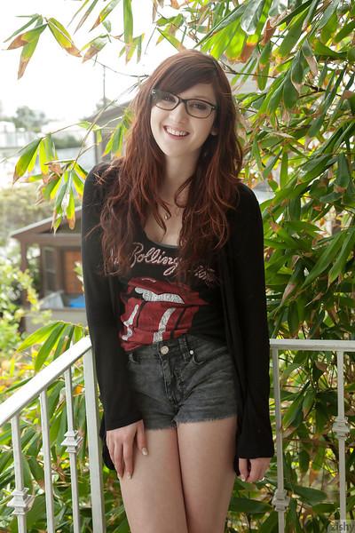 Attractive redhead adolescent Ellena Woods widening her legs on her couch