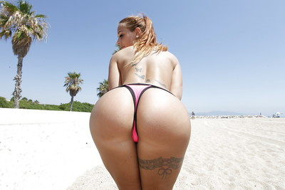 Tattooed girl with mammoth love muffins Kyra Damp shows off her apple bottoms on a beach