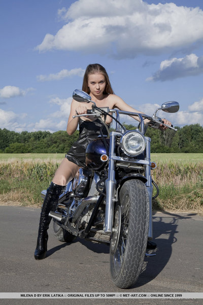 Wearing a extreme leather clothing and boots Milena displays her small and nubile body on dominant of a motorcycle