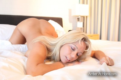 Amber Lynn Bach rolls around the couch extremely unclothed and masturbates.