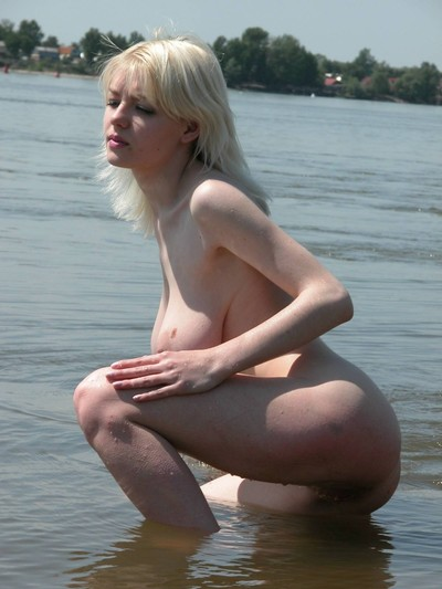 Elegant golden-haired coco is caught posing unclothed on a public beach