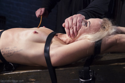 Dylan is restrained in wooden stocks around her neck and wrists. her ankles are