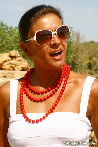 Elderly UK dame Lady Sarah playing with miniscule wobblers outdoors in sunglasses