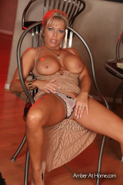 Fascinating MILF Amber Lynn Bach shows off her breasty figure naked.