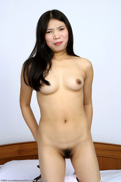 Bushy Japanese adolescent Diep posing bare on her ottoman and swelling her legs