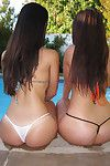 Young dark brown cuties with extreme booties posing in bikinis outdoor