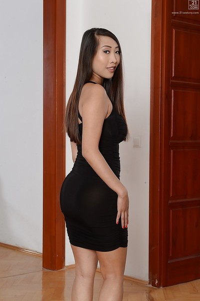Slender Asian cutie Sharon Lee posing fully clothed in tense brown dress