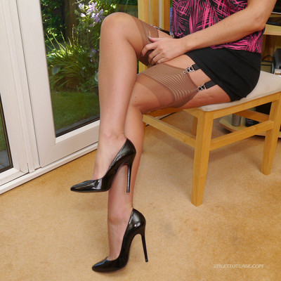 Beauty showes her legs in tan stockings and black heels