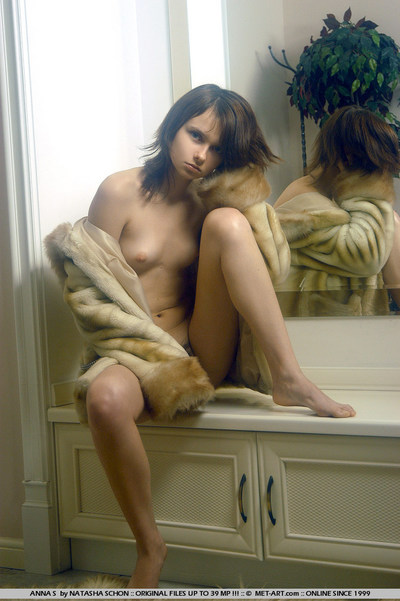 Short haired brunette admires self in mirror while covered only in a mink coat.