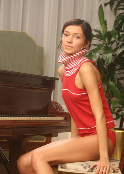 Seductive young juvenile playing with herself by the piano