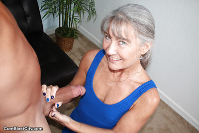 Aged grey haired woman jerks chunky cock POV style for cumshot on granny tits