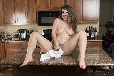 Done cleaning in the kitchen, Felicia F strips and climbs on the counter in her lingerie and denim shorts. On the counter, that babe gets naked to show off her appealing all-natural body full of hairy beauty for us.