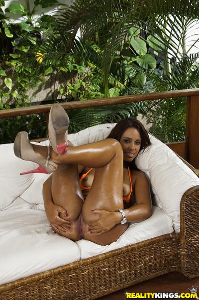 Oiled Brazilian model Cris Brasil letting tanned love melons free from bikini