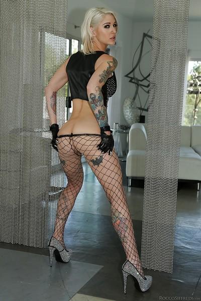 Inked blonde pornstar Kleio Valentien posing against stripper pole