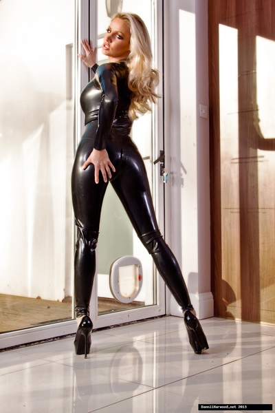 Untamed domesticated golden-haired Dannii Harwood shows off her crooks around the house in a stunning black leather catsuit!