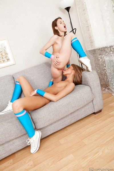 Lovely teen cheerleaders involving knee socks have some lesbian fun on a sofa