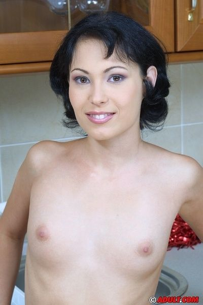 Smiley brunette cheerleader undressing plus exposing her goods in the scullery