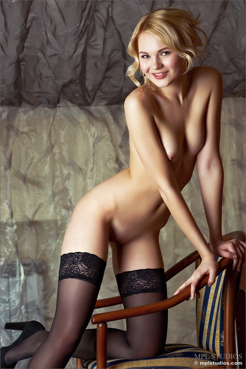 Gorgeous blonde strips down to nothing but sexy black stockings