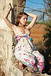 Emily 18 sits on a fluster outdoors in say no to cute flowered dress and she smiles within reach th